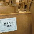 "empty church with ""this pew closed"" sign"